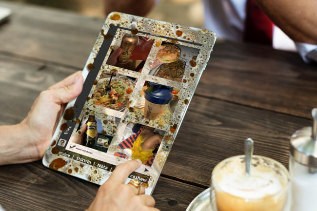 Persoon kiest kipkerrie op een tablet die vettig en vies is door het doorgeven
